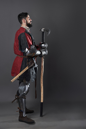 Medieval knight on grey background. Portrait of brutal dirty face warrior with chain mail armour red and black clothes and battle axe. Stockfoto - 101403692