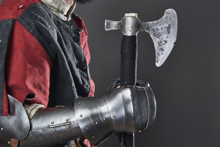 Medieval knight on grey background. Portrait of brutal dirty face warrior with chain mail armour red and black clothes and battle axe. Фото со стока