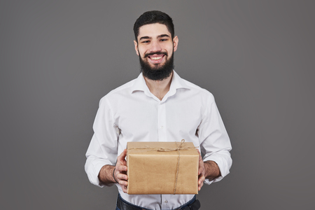 With love for you. Good looking young man in blue jeans shirt holding a gift box and looking at camera while standing against grey background.