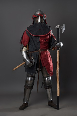 Medieval knight on grey background. Portrait of brutal dirty face warrior with chain mail armour red and black clothes and battle axe. Banco de Imagens