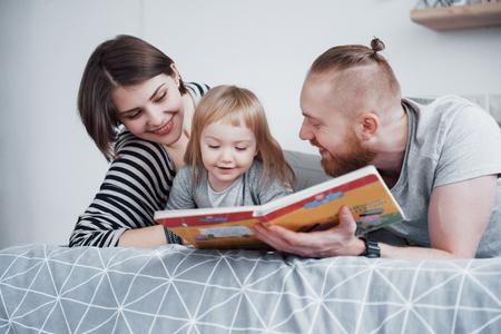 Father, Mother and Little Daughter Reading Childrens Book on a Sofa in the Living Room. Happy big family read an interesting book on a festive day. Parents love their children. Stockfoto
