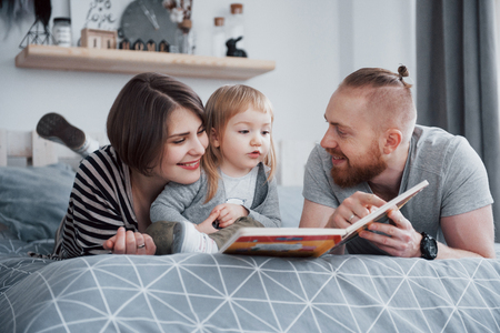 Father, Mother and Little Daughter Reading Childrens Book on a Sofa in the Living Room. Happy big family read an interesting book on a festive day. Parents love their children. Stock Photo