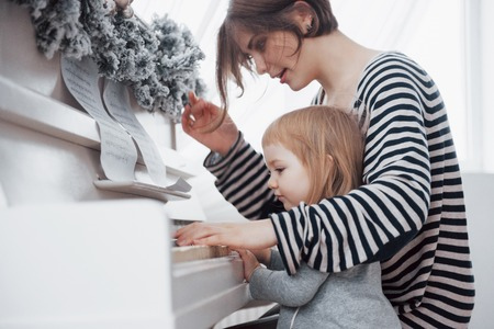 mother and daughter playing white piano, close up wiew. Stock Photo