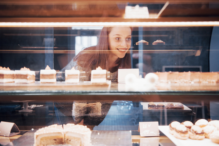 Smiling woman at camera through the showcase with sweet and cakes in modern cafe interior. Stock Photo