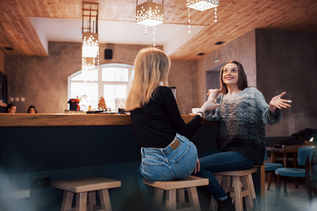 Two girl friends drinking coffee in the cafe. Imagens