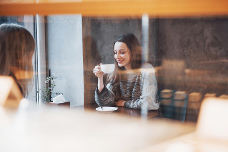 Two friends enjoying coffee together in a coffee shop as they sit at a table chatting. Stock Photo