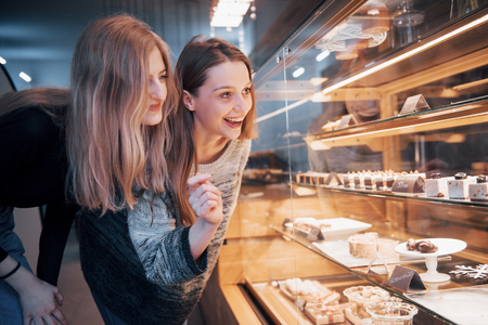 Two happy attractive girls choosing delicious ganaches, praline and chocolates.