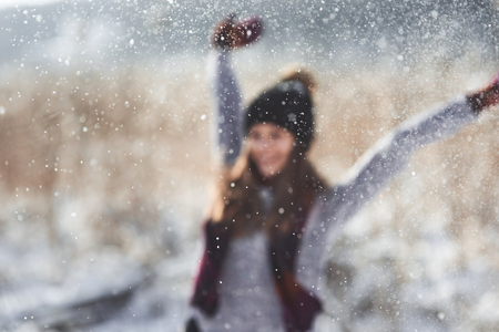 Beauty Winter Girl Blowing Snow in frosty winter Park. Outdoors. Flying Snowflakes. Sunny day. Backlit. Joyful Beauty young woman Having Fun in Winter Park. Defocused.