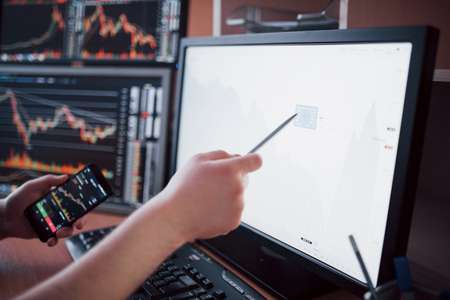 Analyzing data. Close-up of young businessman pointing on the data presented in the chart with pen while working in creative office. Stock Photo