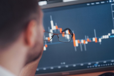 Analyzing data. Close up of a young businessman who holds glasses and looks at the gff while working in a creative office.