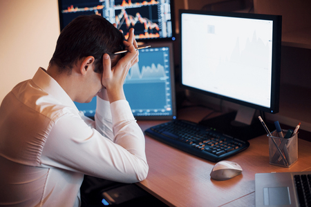 Stressful day at the office. Young businessman holding hands on his face while sitting at the desk in creative office. Stock Exchange Trading Forex Finance Graphic Concept. Stock Photo