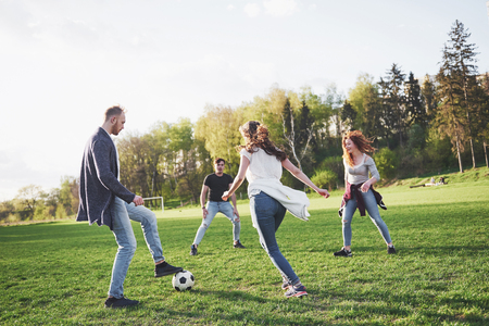 A group of friends in casual outfit play soccer in the open air. People have fun and have fun. Active rest and scenic sunset. Imagens