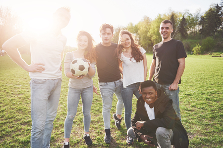 A group of friends in casual outfit do sephi on the soccer field. People have fun and have fun. Active rest and scenic sunset.