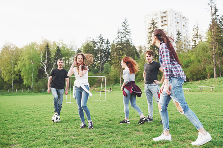 A group of friends in casual outfit play soccer in the open air. People have fun and have fun. Active rest and scenic sunset. 写真素材