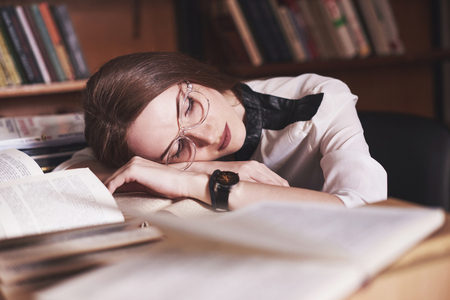 A young girl student is tired in the reading room of the old library.