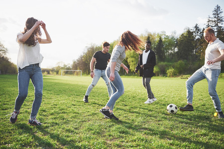 A group of friends in casual outfit play soccer in the open air. People have fun and have fun. Active rest and scenic sunset. Stok Fotoğraf