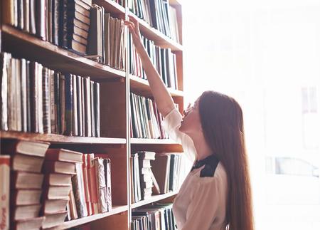 Młoda studentka szuka odpowiedniej książki na półkach starej biblioteki uniwersyteckiej.