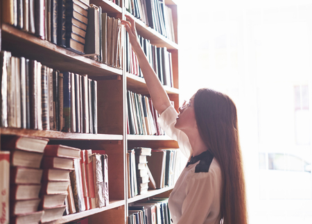 Una giovane studentessa sta cercando il libro giusto sugli scaffali della vecchia biblioteca universitaria.