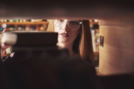 A young student girl is looking for the right book on the shelves of the old university library.