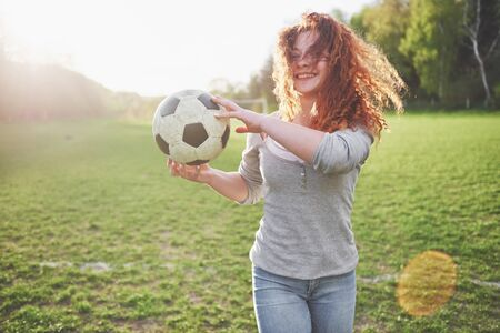 Young redhead sexy girl in casual player in soccer stadium at sunset.