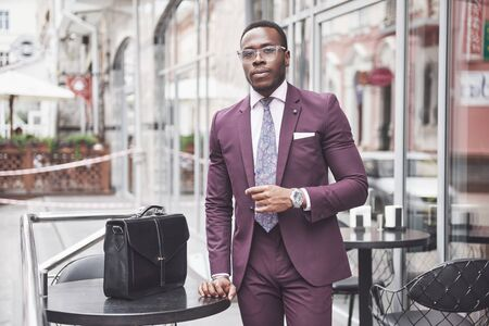 Young businessman with a briefcase near a beautiful office. Business meeting.