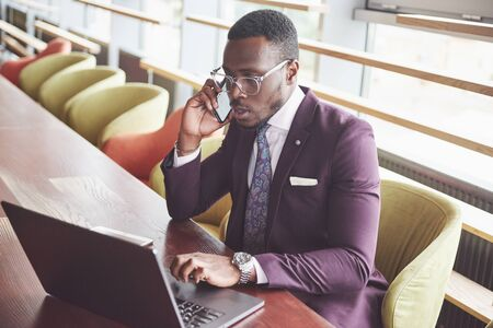 A beautiful stylish African American businesswoman wearing a suit uses his laptop while working.