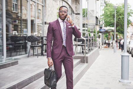 Porträt eines jungen schönen Afroamerikanergeschäftsmannes mit einem Aktenkoffer. Geschäftstreffen