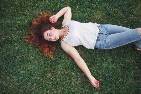 Ragazza rilassante con rosso, sdraiata sull'erba. La donna si rilassa all'aperto