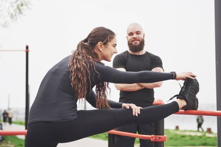 Young man and woman perform exercises and stretch marks before doing sports.