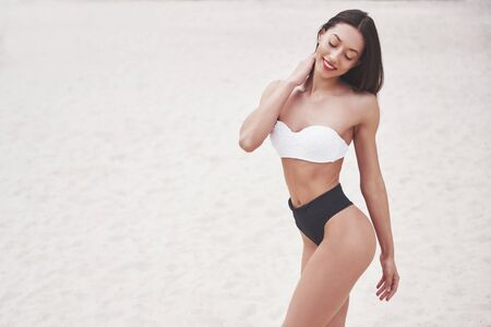 Beautiful slim luxury girl in bikini on the sand beach on a tropical island. Sexy tanned body and perfect figure.