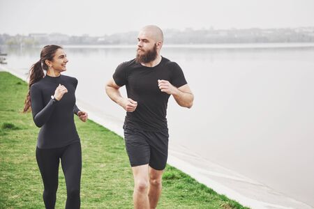 Couple jogging and running outdoors in park near the water. Young bearded man and woman exercising together in morning.