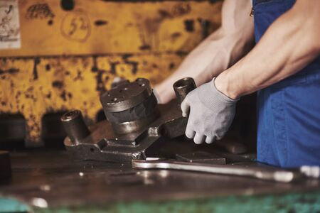 Strong hands hold the steel part. In the old factory Standard-Bild - 134368266