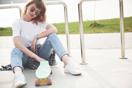 A photo of a beautiful girl with beautiful hair holds a skateboard on a long board, looking at the camera and smiling, urban life Stock Photo