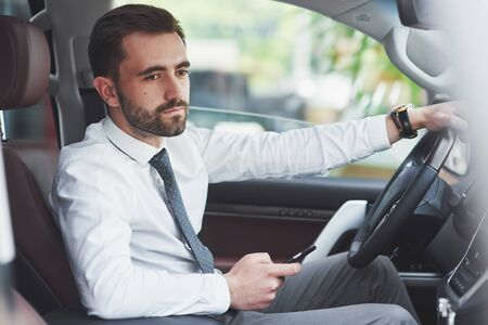 Beautiful young man in full suit while driving a car.