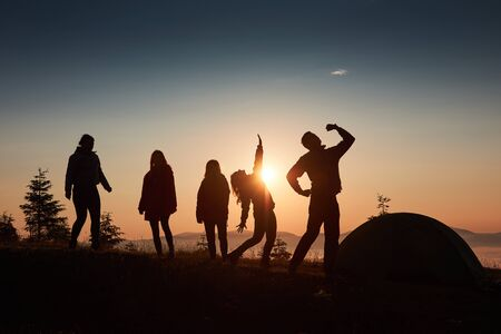 A silhouette of group people have fun at the top of the mountain near the tent during the sunset.