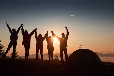 A silhouette of group people have fun at the top of the mountain near the tent during the sunset. Stockfoto - 134368833