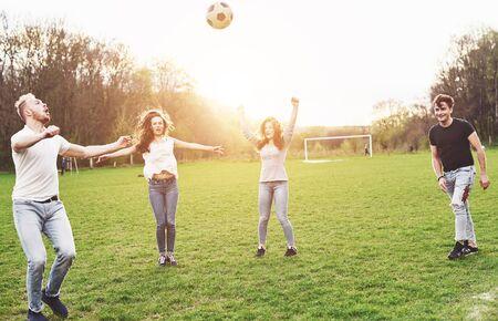 Un grupo de amigos en ropa casual juega al fútbol al aire libre. La gente se divierte y se divierte. Descanso activo y puesta de sol escénica Foto de archivo