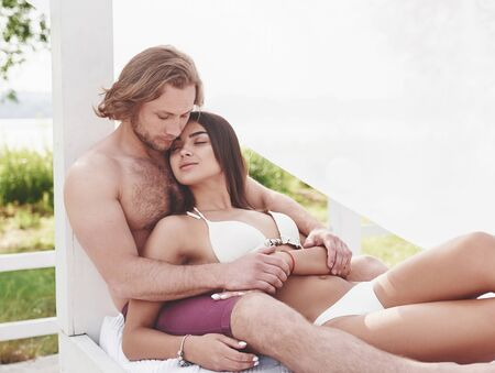 A beautiful couple relaxing on the sandy beach, wearing bathing clothes. Romantic atmosphere