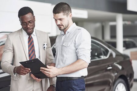 An African American with a consultant at a car dealership chooses a car. Good bargain