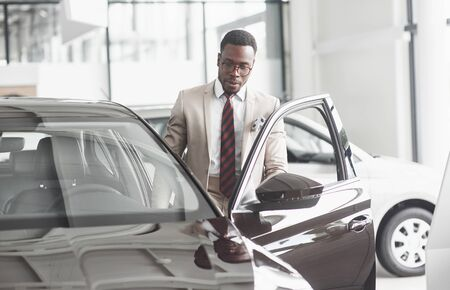 An African American inspects the car at the car dealership. Good bargain