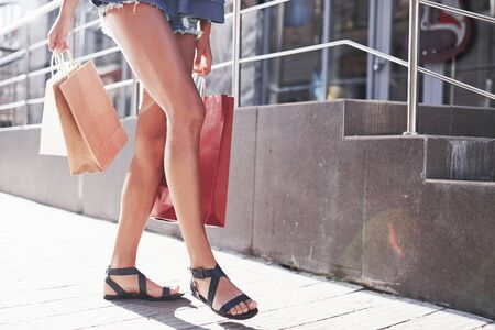 Closeup of woman holding shopping bags on the street in summer day.