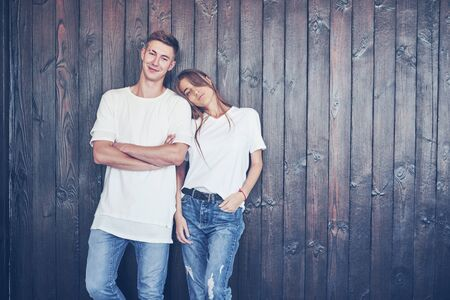 Young couple, guy and girl together on a wooden wall background. They are happy together and dressed alike. Always in a trend. Imagens