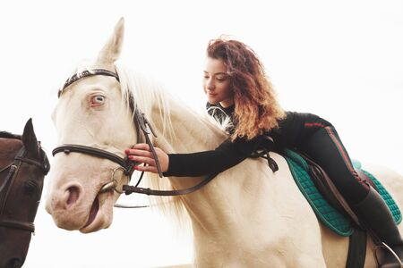 Young cute girl hugging her horse while sitting astride. She likes animals.