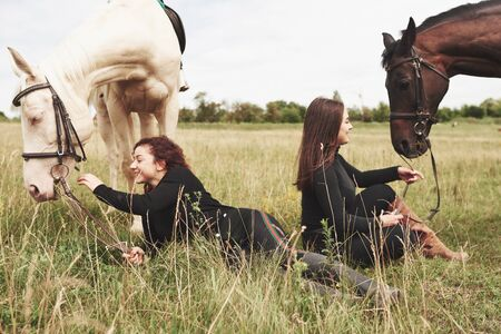 Two young beautiful girls in gear for riding near their horses. They love animals. Zdjęcie Seryjne