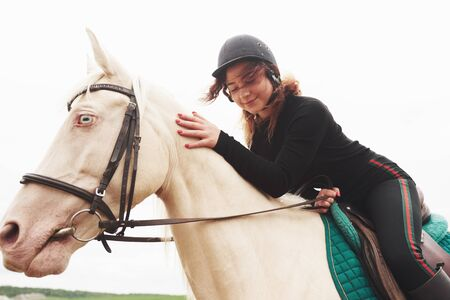 Young pretty girl - riding a horse, equestrian sport in spring time.