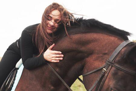 Giovane ragazza carina che abbraccia il suo cavallo mentre è seduto a cavalcioni. Le piacciono gli animali.