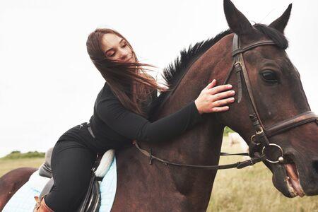 Junges nettes Mädchen, das ihr Pferd beim Sitzen rittlings umarmt. Sie mag Tiere. Standard-Bild