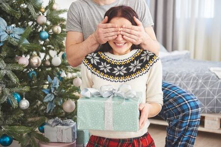 Young couple celebrating Christmas. A man suddenly presented a present to his wife. The concept of family happiness and well-being.