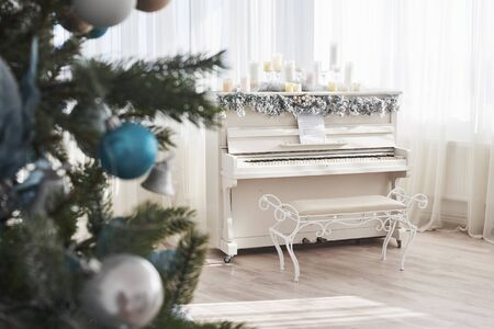 New Year decoration. Christmas tree near white piano at the window background.