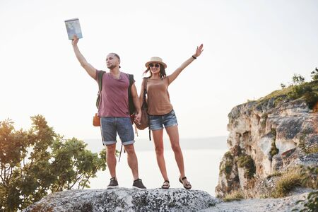 Two tourist male and woman with backpacks stand to the top of the crag and enjoying sunrise. Traveling mountains and coast, freedom and active lifestyle concept.